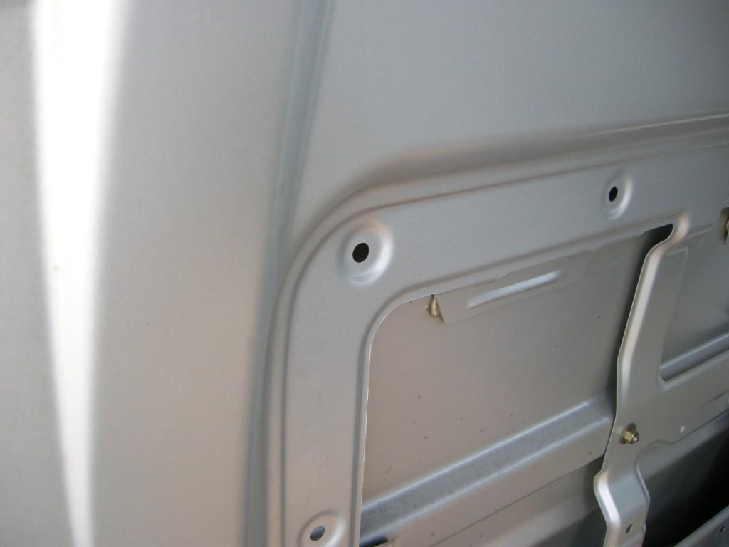 写真A:ボディにあるグロメット穴/このように、ボディの鉄板に直接穴が開いている場合は、これを利用してアンカーナット+ボルトを使えば、ある程度の強度は期待できる。それでもボディの鉄板は意外と薄いので、過信は禁物。
